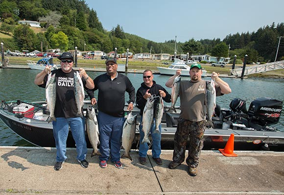 A limit of winchester bay salmon being held by happy customers of guide, lance fisher