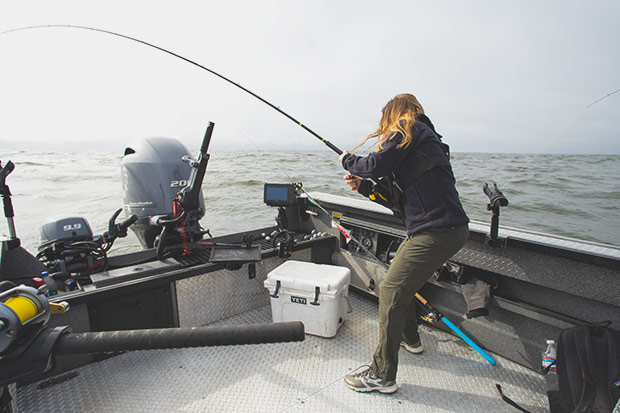 A lady fighting a Salmon on the ocean in front of Astoria Oregon