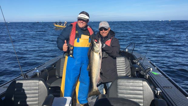lance fisher and guest with large tillamook salmon in tillamook bay