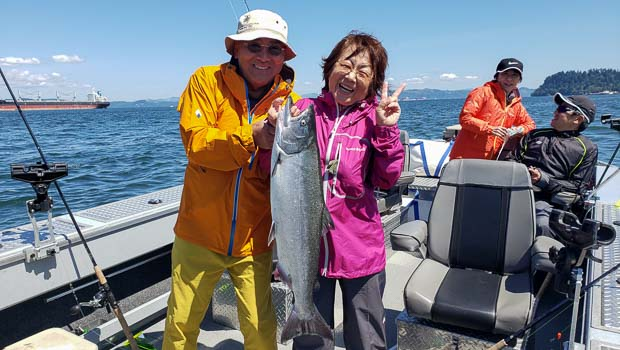 Happy couple with their Columbia River Chinook Salmon at Buoy 10 in Astoria